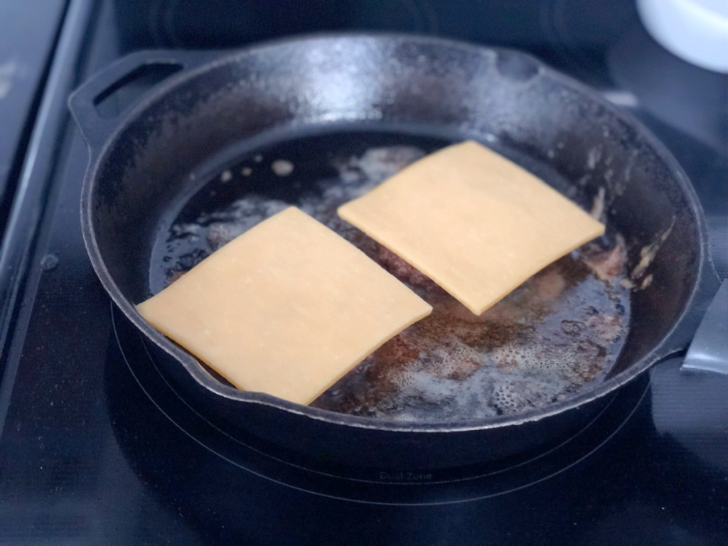 cheese on burgers in a skillet