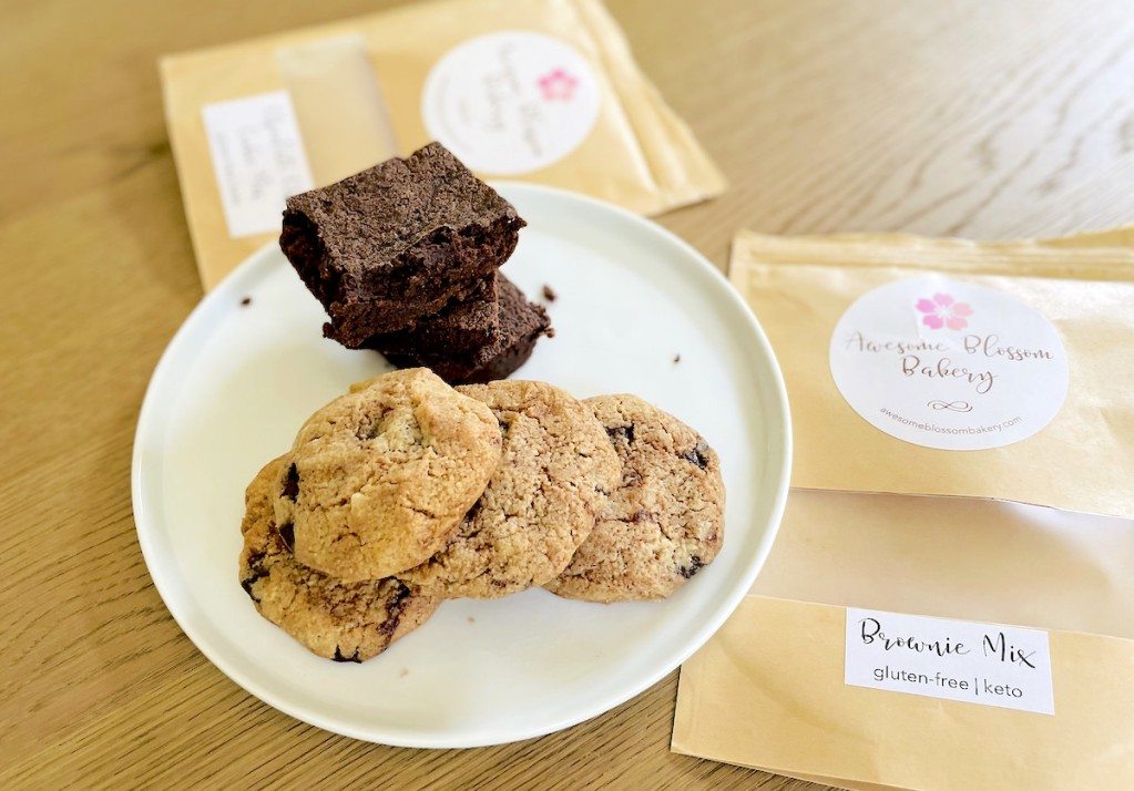awesome blossom baking mixes on table with keto brownies and cookies on white plate