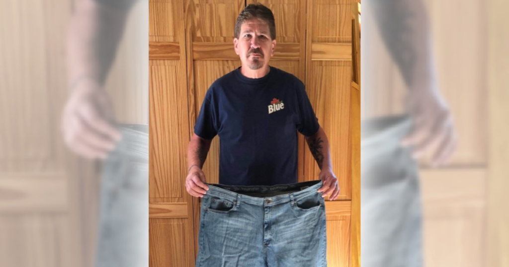 man holding large pair of pants after keto success weight loss