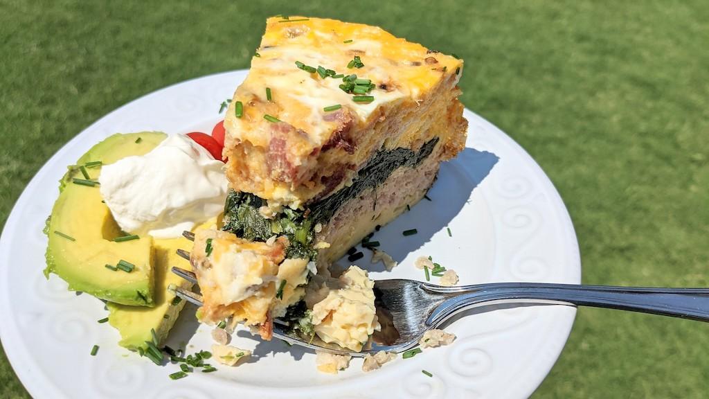 keto breakfast slice on plate with sour cream & avocado