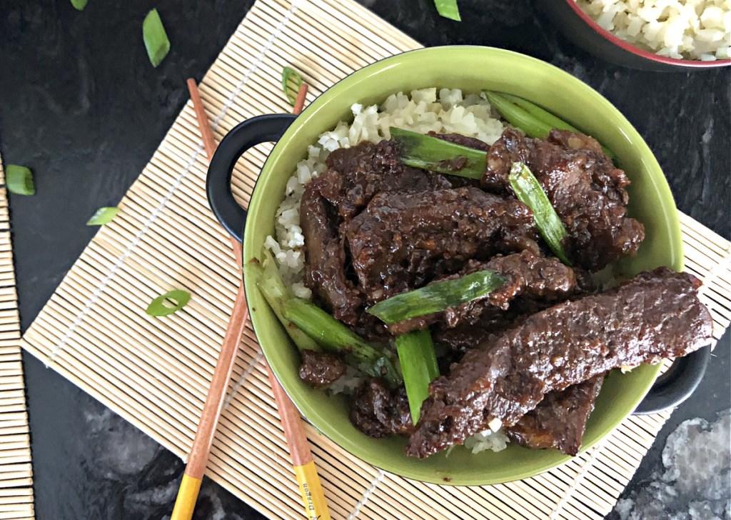 keto crockpot mongolian beef in green bowl with chopsticks