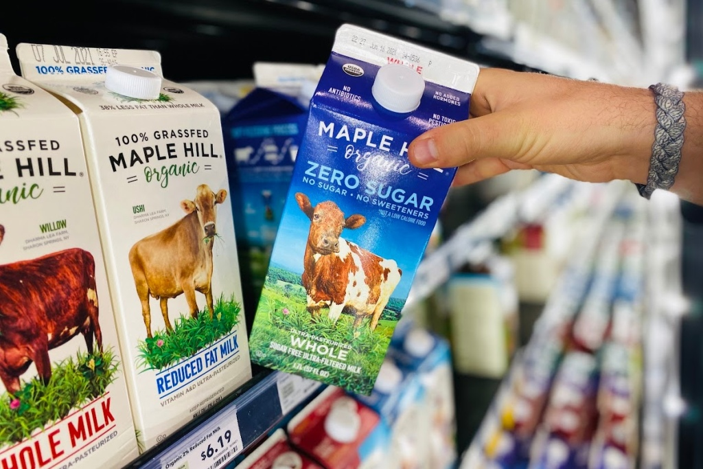 Hand pulling out a carton of Maple Hill zero sugar milk