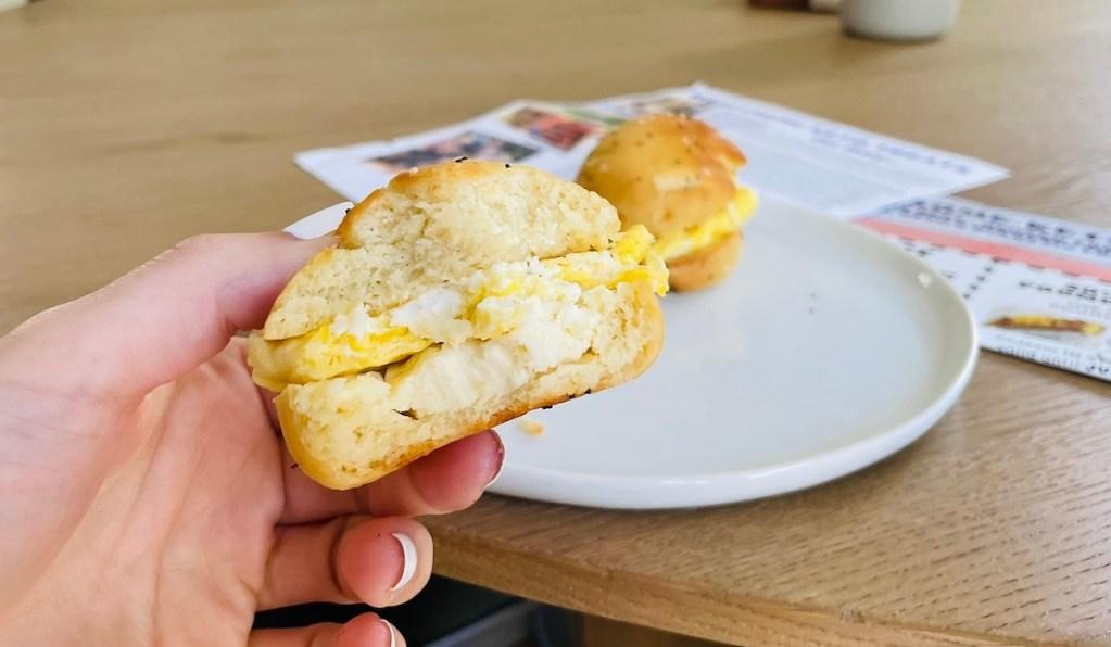 hand holding everything bagel egg sandwich