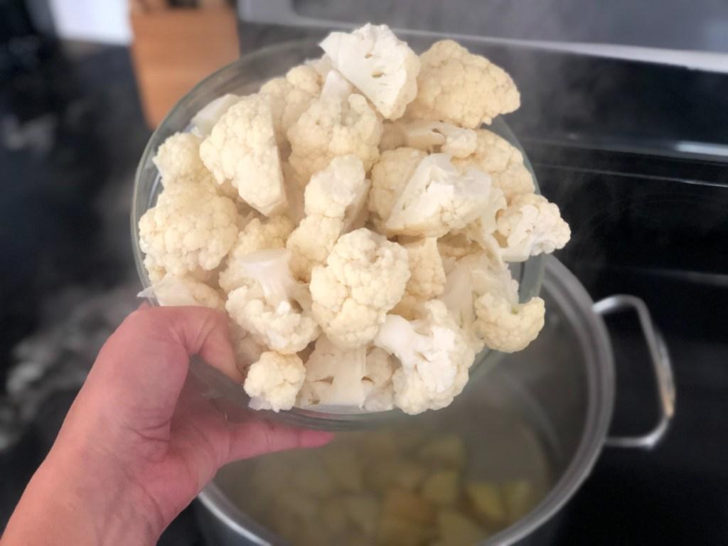 adding cauliflower to a stockpot