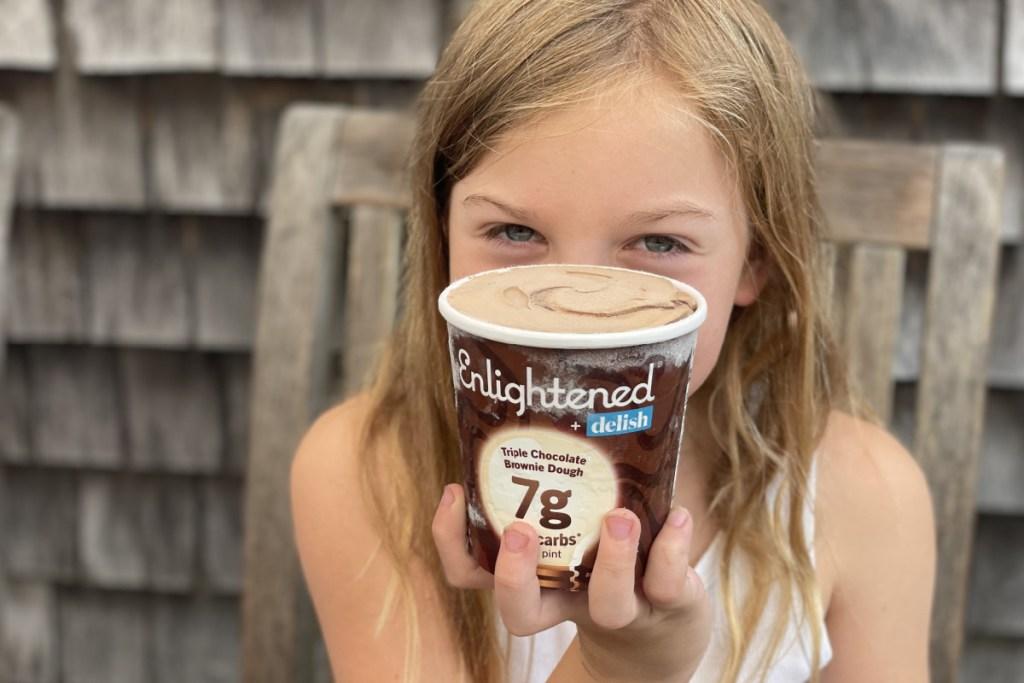 little girl holding pint of Enlightened keto ice cream