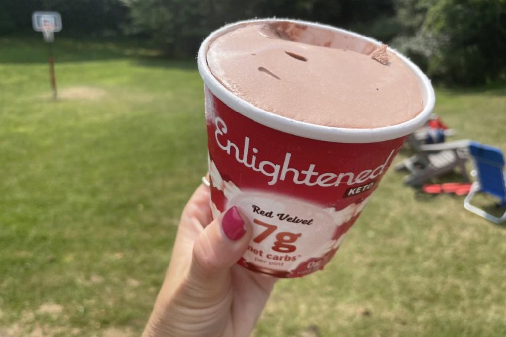 Holding a pint of ENlightened red velvet keto ice cream