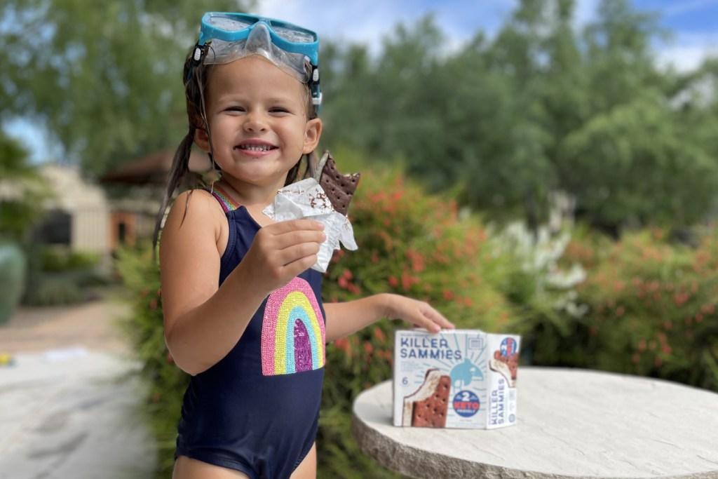 girl eating keto ice cream sandwich near pool