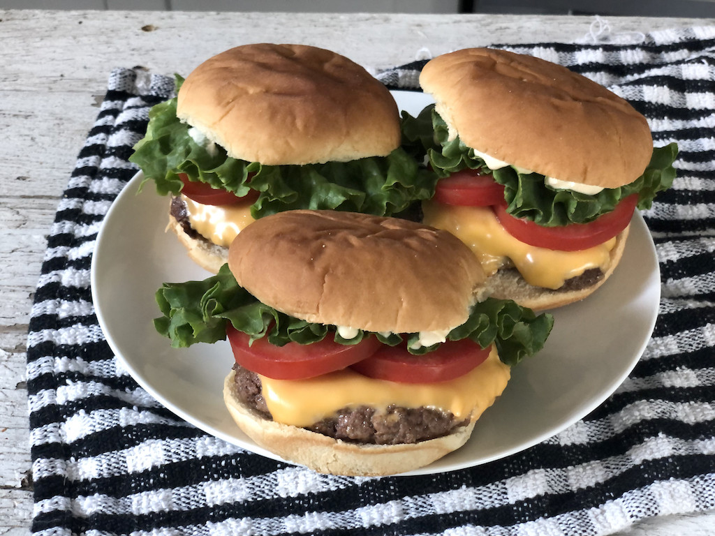 keto cheeseburgers on plate with all the fixings