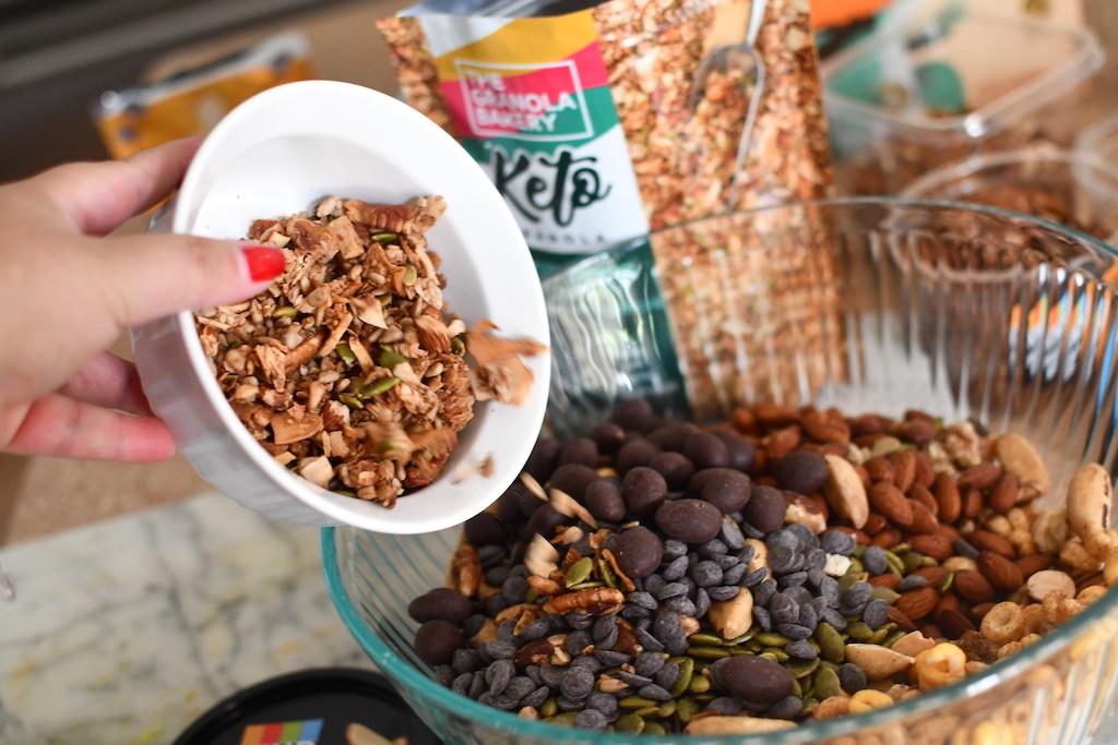 putting keto trail mix ingredients in bowl