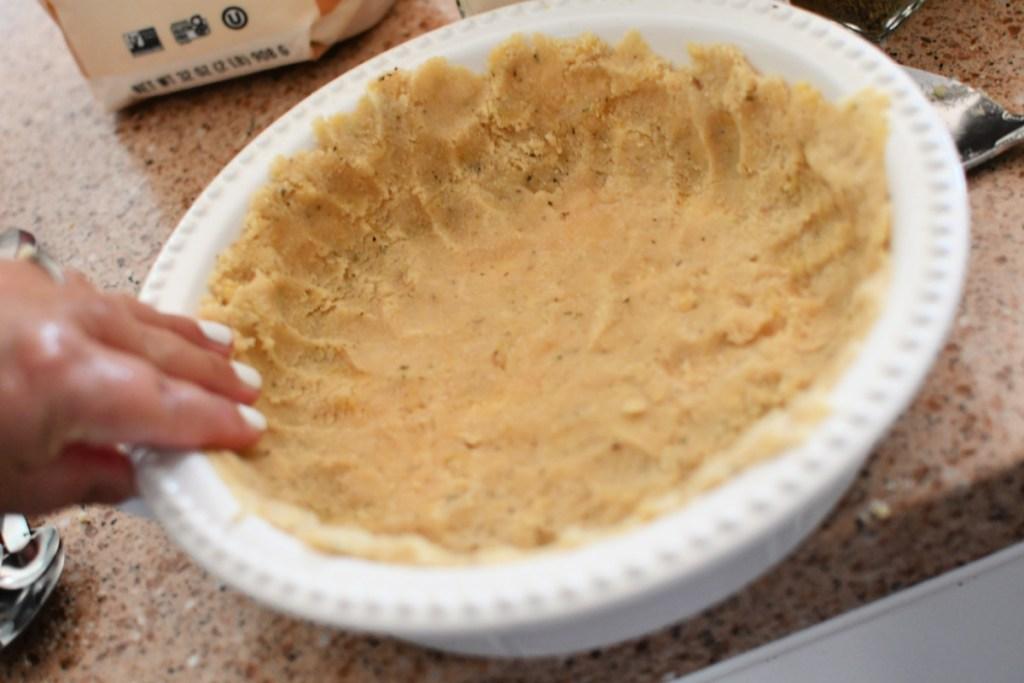 pressing a keto pie crust into pan