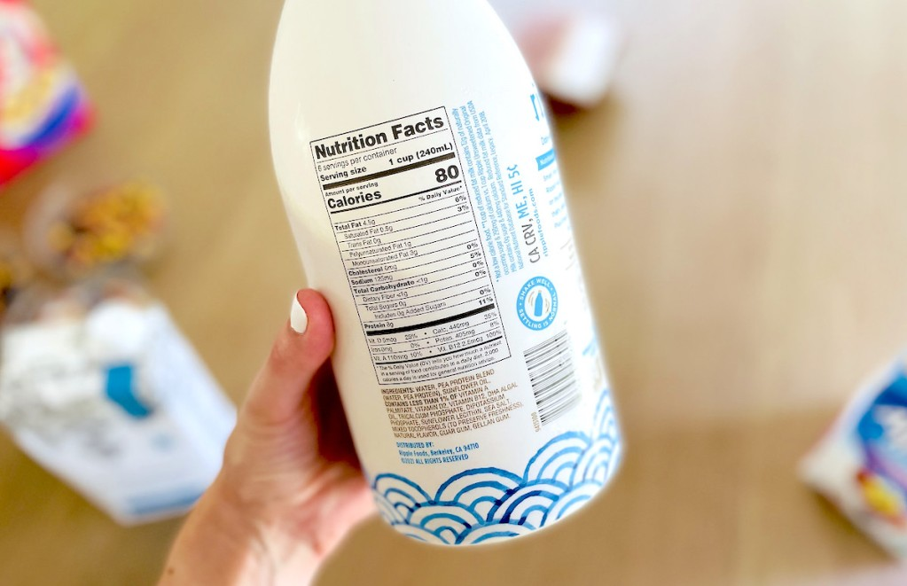 hand holding a container of ripple dairy free milk with ingredients label showing