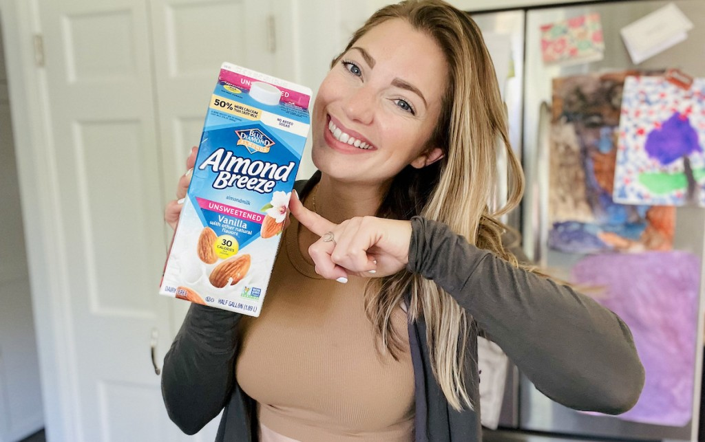 woman holding up carton of almond milk in kitchen