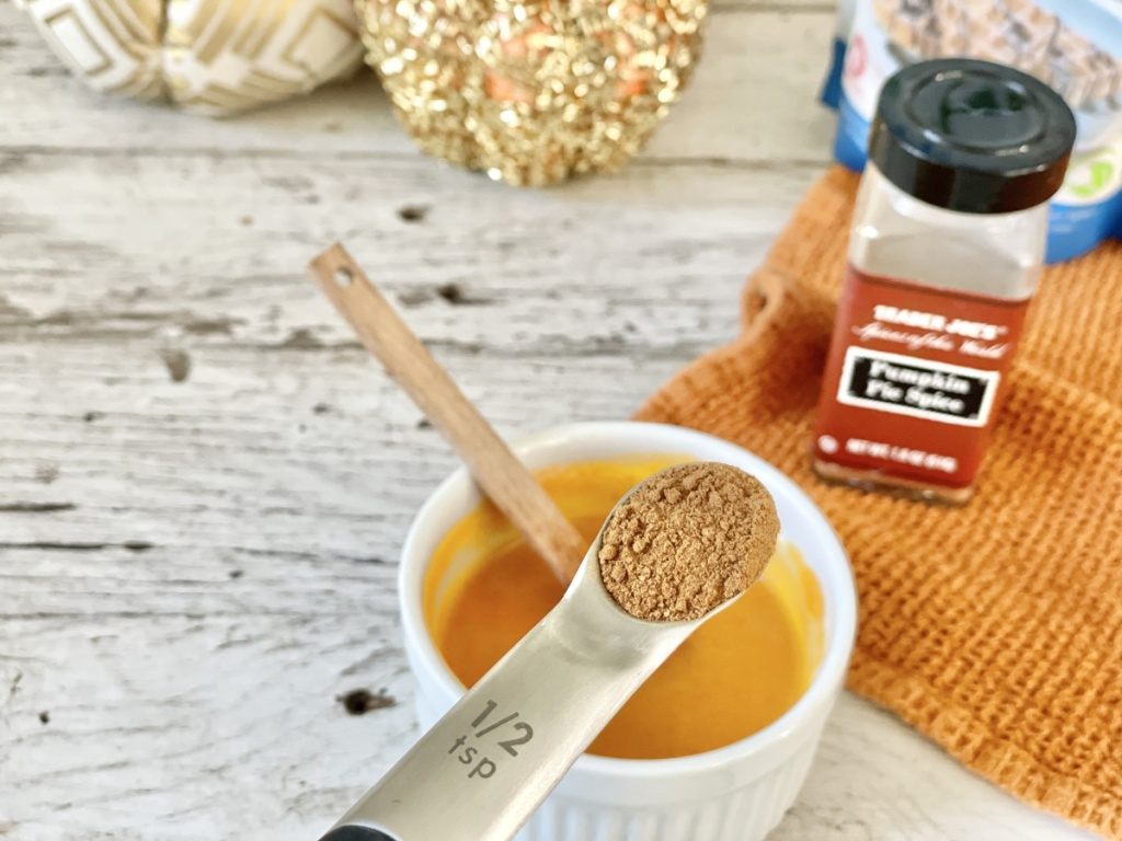Keto Pumpkin Mug Cake batter adding pumpkin pie spice