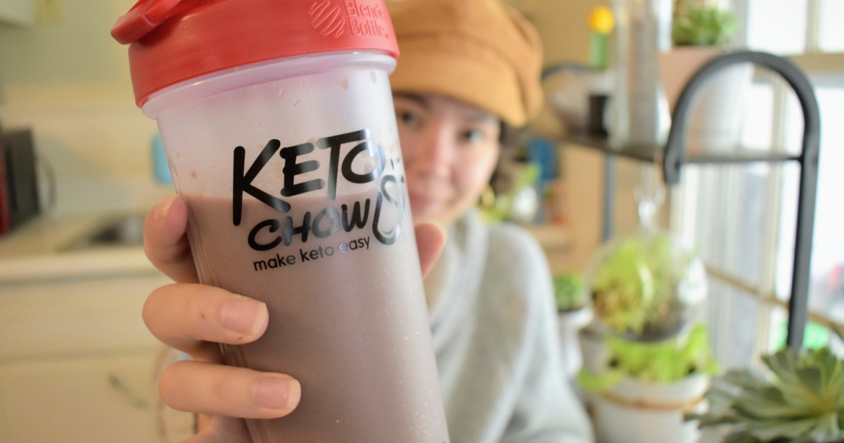 holding Keto Chow meal replacement protein shake in bottle
