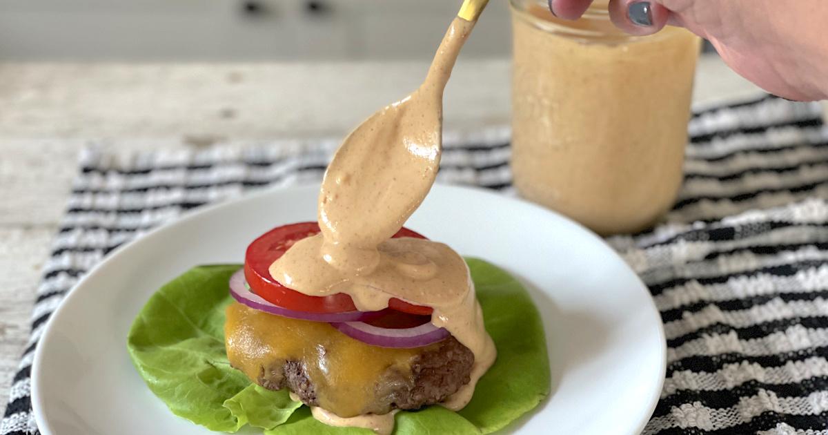 putting keto burger sauce on burger