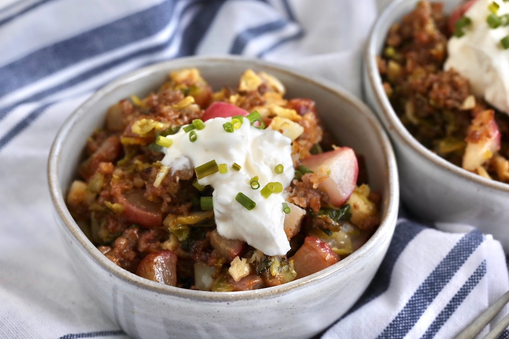 close up of keto sausage hash with sour cream in a bowl