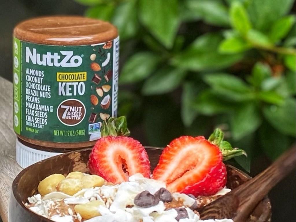 jar of chocolate Nuttzo next to breakfast bowl